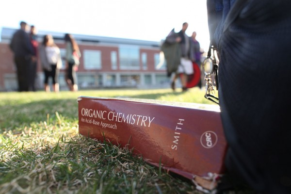 Closeup of a textbook lying on the grass outside the Student Union